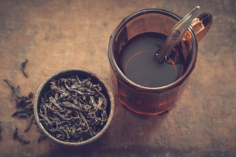 Vintage mug of tea and rustic metal cup of dry tea leaves.