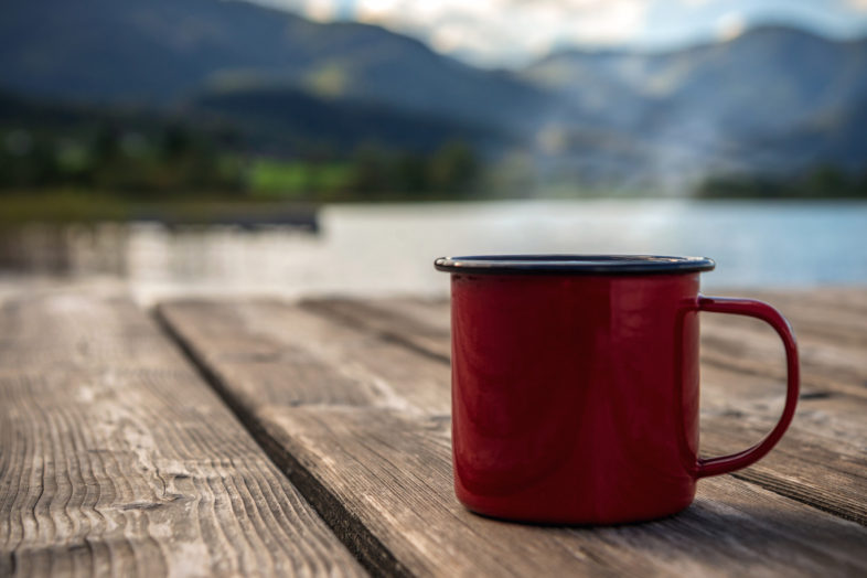 Outdoor-adventure concept: red mug on a lake