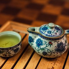 Fine ceramic small blue chinese teapot with a small tasting cup full of oolong tea - Shot during a gong fu cha tea ceremony with a very small teapot on a tea boat